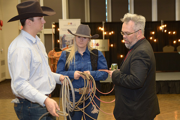 In this photo: Rodeo Team teaches delegate about roping